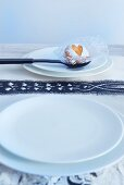 White plate, black spoon with biscuit on doily and printed paper table mat