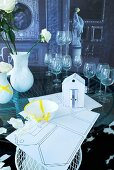 Wedding symbols; paper house model, broken crockery stuck together with yellow tape, stemware and vases on glass table