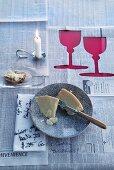 Tischdecke aus Zeitungspapier mit ausgeschnittenen Weinglas-Silhouetten, bekritzelter Serviette und Kerzenhalter in Löffelform
