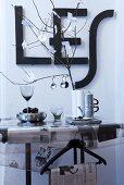 Schwarz-weisse Tischdeko mit Zeitungspapier, Zweig mit Zettelblättern und an die Wand gehängten Buchstabenformen