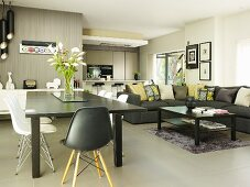 Shell chairs and grey dining table next to lounge area with corner sofa and kitchen area in background in modern, open-plan interior with grey tiled floor