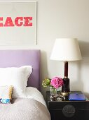 Vintage lamp on bedside cabinet next to double bed with lilac headboard and text artwork on wall
