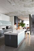 View from designer kitchen with island counter into open-plan living area with staircase, polished concrete floor and unfinished concrete ceiling