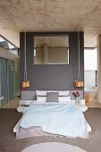 Elegant, purist, designer bedroom with mirror on grey partition and access to ensuite bathroom