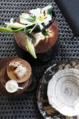 Lilies, coffee cup and slice of cake arranged on wooden boards