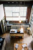Spacious, vintage kitchen in loft apartment in old industrial building with wooden floor and brick walls