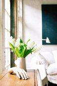 Still-life arrangement of plaster hand and vase of white hyacinths in loft-apartment interior