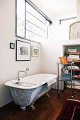 Vintage bathtub below window and fitted partition elements in loft apartment in renovated industrial building