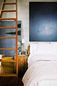 Bed with white bed linen below dark painting next to long wooden ladder and wooden box used as bedside table