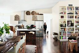 Shelving, dining table with rustic wooden top, woman and dog in background and wicker lamps in kitchen in modern, open-plan interior