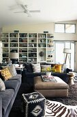 African occasional furniture, zebra-skin rug, grey sofa set with scatter cushions and ottoman in front of white shelving