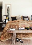 Rustic Chinese wooden bench at foot of simple double bed with ethnic bedspread in shades of brown and scatter cushions