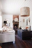 Stacks of scatter cushions on ecru sofa, dark wooden trunk on wooden floor, pendant lamp with large cylindrical lampshade hanging from white wooden ceiling and rustic fireplace