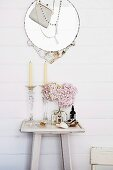 Glass candlesticks and vase of pink hydrangeas on white-painted console table below round mirror decorated with necklace and handbag on wooden wall