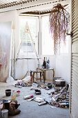 Corner of studio - used tubes of paint and painting utensils on floor, easel and side table in window bay, branches hung from wooden beams below corrugated metal ceiling