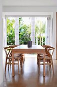 Simple elegant wooden table, Hans Wegner wooden chairs and view into garden with palm trees