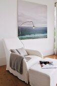 Comfortable white loose-covered armchair, reading lamp, pouffe and peaceful seascape painting