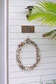 Delicate wreath below house number and lamp on white wooden façade behind palm frond