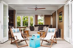 Wooden deckchairs and pale blue vintage wooden box used as side table in front of open-plan living area of bungalow with sand-coloured walls