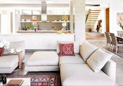 White furnishings in open-plan living area in designer apartment