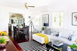 Comfortable, country-house living area with black and white striped rug, white sofa, dining area and view into kitchen