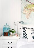 Light blue birdcage and vintage bedside lamp on white bedside cabinet with drawers next to bed with zig-zag pillow below map on wall
