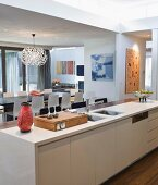 View past 60s ornaments on kitchen counter into open-plan living room with Dandelion designer lamp above dining table