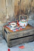 Rusty tray, vintage teacup and Chinese china teapot on weathered wooden crate used as side table against rustic wooden wall
