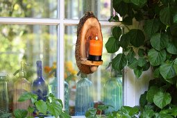 Candle sconce hand-crafted from slice of tree trunk on lattice window with vintage soda siphons on windowsill