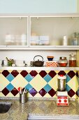 Vintage tiles and granite kitchen worksurface below wall cabinets with frosted glass fronts