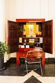 Folding chair in front of red, Chinese wedding cabinet with wide open doors and view of shrine-style arrangement inside
