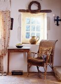 Kitten and tapestry cushion on wicker chair below lattice window in historical, French farmhouse