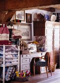 Small, crammed sewing room with antique furniture, ornaments and stacks of handmade cushions in vintage fabrics