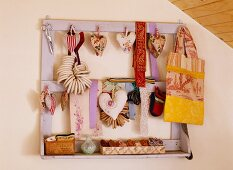 Heart-shaped pincushions made from vintage, French fabrics, fabric bag and ribbons hanging on old wooden rack