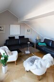 Attic living room with fur blanket on white armchair and black leather sofa set around DIY coffee table