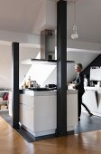 Kitchen area in converted attic, woman at white island counter on grey tiled floor behind black-painted wooden pillars
