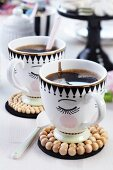 Painted coffee cups with coasters made from wooden beads