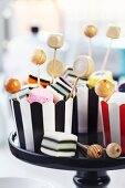 Wooden beads on toothpicks in striped cupcake cases of liquorice allsorts