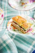 Tomato and mozzarella focaccia sandwich on floral plate and white and blue checked woollen blanket