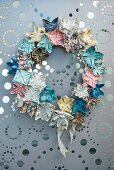 Artistic wreath of small, pastel origami flowers hung on grey metal panel with perforated pattern