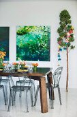 Flower arrangements on solid wooden table and smoked plastic chairs; photos of plants and large branch decorated with origami Christmas garland
