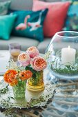 Australian Christmas arrangement of Ranunculus and roses in ornate glasses and candle lantern on tray on coffee table