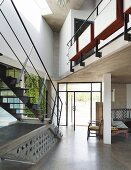 Purist steel staircase and glazed door element in foyer of contemporary house with gallery