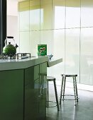 Island counter with lowered breakfast bar in designer kitchen with pastel green tip-on doors