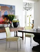 Chairs with green and white graphic upholstery at table, rustic console table with vases of flowers, floor-to-ceiling doorway and view of coat stand