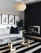 Coffee table with glass top on wooden base and black and white striped rug in front of black and white sofa below pictures on wall; open fireplace in black wall to one side
