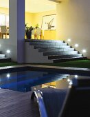 Pool in front of illuminated steps leading to dining area on platform in yellow-painted interior