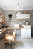 Swivel chair with armrests at corner desk, chest of drawers and wall cabinet on wall painted pale grey