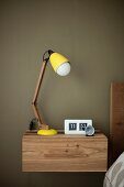 Retro, yellow table lamp on modern, wooden, wall-mounted bedside cabinet