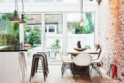 Modern dining area and island counter with bar stools in open-plan kitchen with exposed brickwork